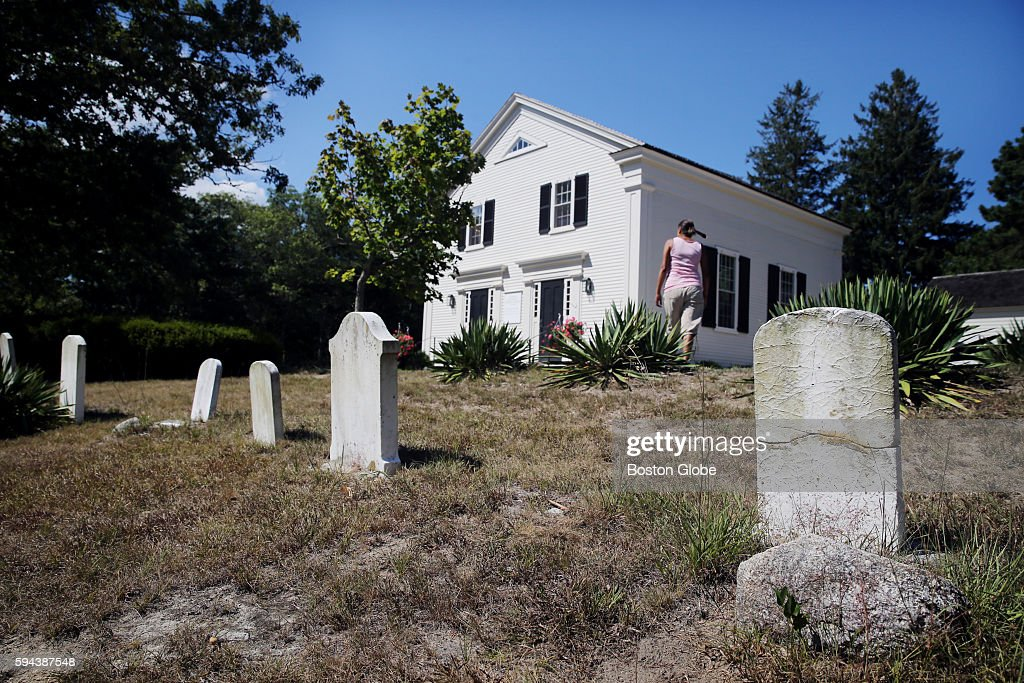Caretaker Naomi Walker passes through the cemetery outside the Mashpee Old Indian Meeting House in Mashpee Mass on August 2016