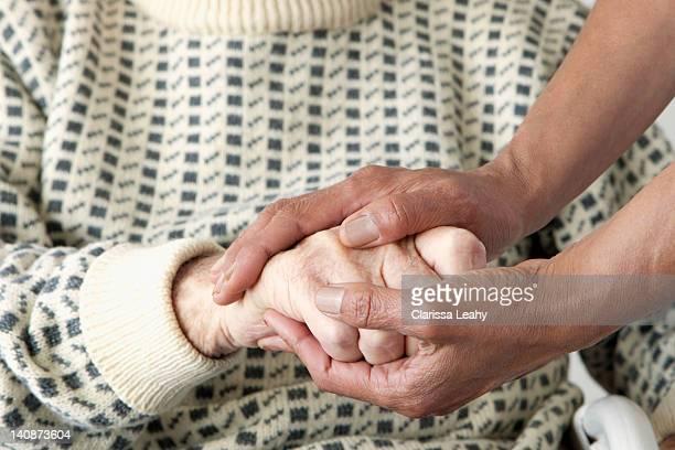 Caretaker patting older mans hand
