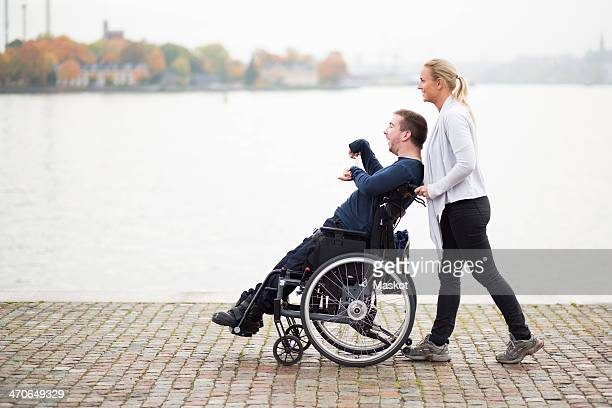 Caretaker pushing disabled man on wheelchair along lake