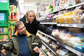 Caretaker shopping with disabled man on wheelchair in supermarket