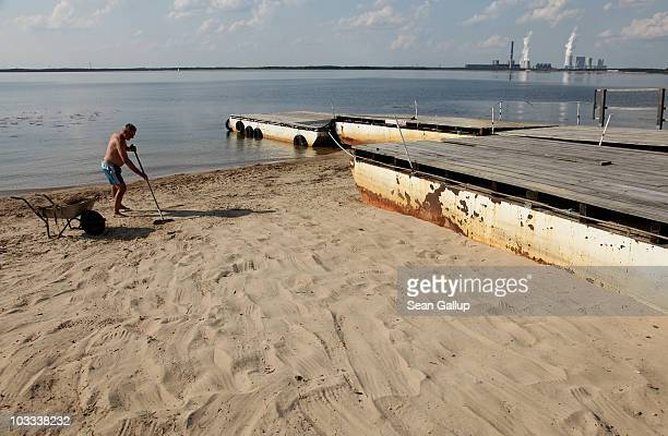 A caretaker sweeps debris from a beach next to a small mooring pier for boats at Baerwalder See lake as exhaust rises from the Boxberg coalburning...