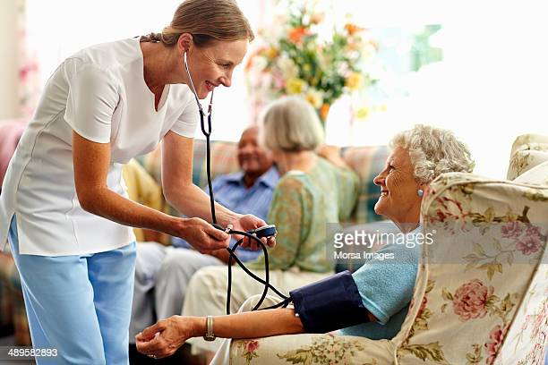 Caretaker taking senior woman's blood pressure
