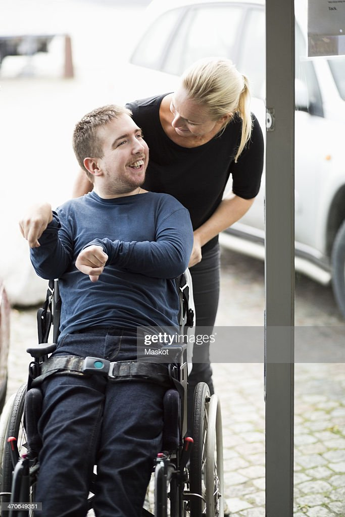Caretaker talking to disabled man on wheelchair outdoors