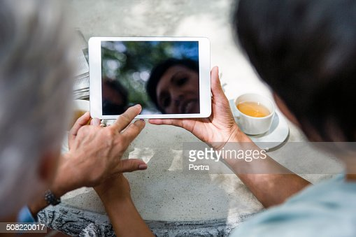 Caretaker using digital tablet with senior woman