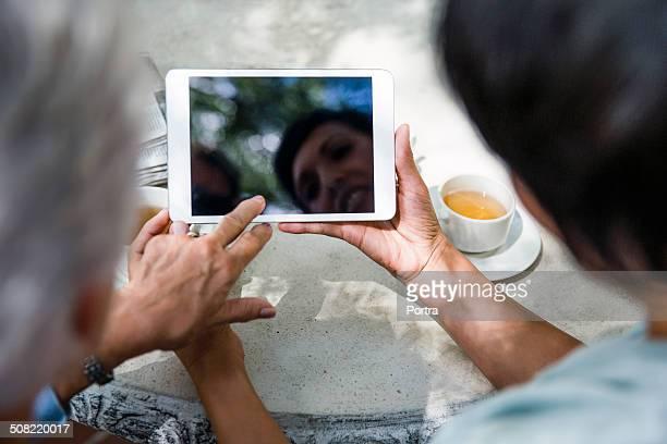 Caretaker using digital tablet with senior woman