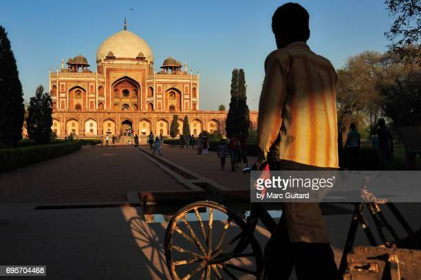 A caretaker using his bike to transport soil at Humayun's Tomb, Delhi, India