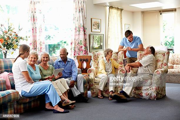 Caretaker with retired people in nursing home