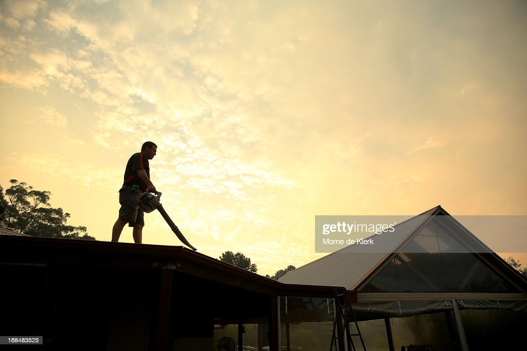 A Carey Gully resident uses a leaf blower to clear dry foilage from his roof in preparation to face a bushfire that is burning out of control at nearby Cherryville on May 10, 2013 in Adelaide, Australia. The out of control bushfire has burned 250 hectares (617 acres) of rugged terrain in the Adelaide Hills, claiming one house, and threatening more property.
