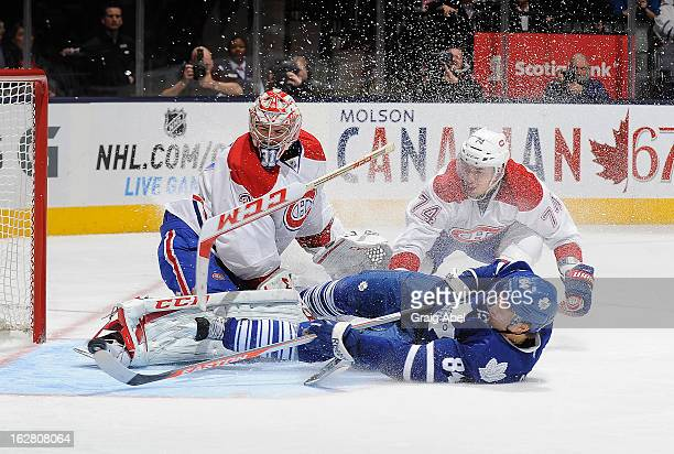 Carey Price and Alexei Emelin of the Montreal Canadiens defend as Mikhail Grabovski of the Toronto Maple Leafs crashes the goal during NHL game...