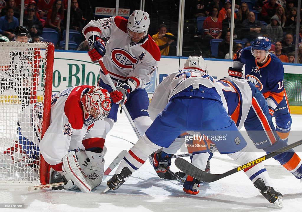 Carey Price #31 and Andrei Markov #79 of the Montreal Canadiens protect the net against the New York Islanders at Nassau Veterans Memorial Coliseum on March 5, 2013 in Uniondale, New York. The Islanders defeated the Canadiens 6-3.