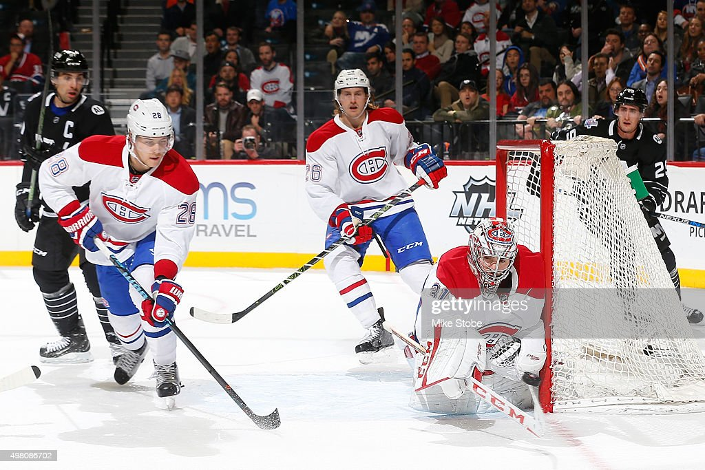 Carey Price makes a save while Nathan Beaulieu and Jeff Petry of the Montreal Canadiens defend the net during the game against the New York Islanders...