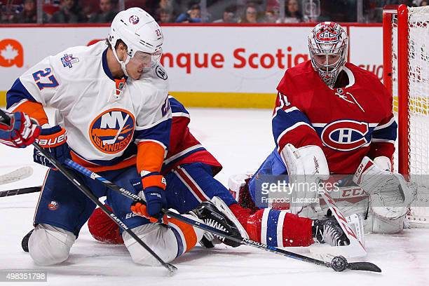Carey Price of the Montreal Canadiens and Anders Lee of the New York Islanders fight for the puck in the NHL game at the Bell Centre on November 22...