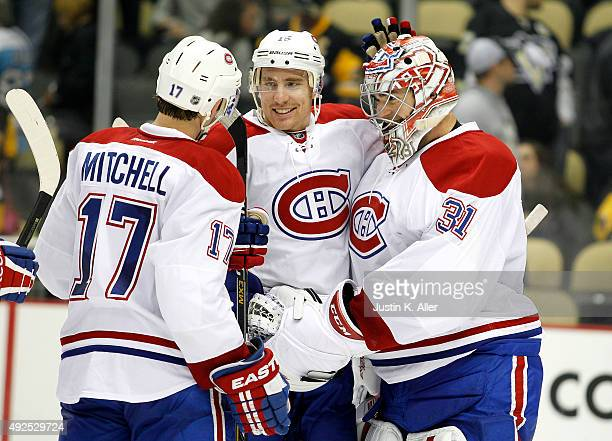 Carey Price of the Montreal Canadiens celebrates with Tomas Fleischmann and Torrey Mitchell after defeating the Pittsburgh Penguins 32 at Consol...