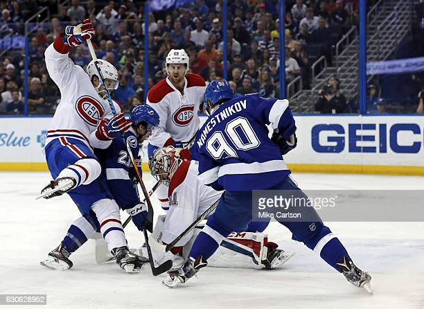 Carey Price of the Montreal Canadiens covers the rebound as Brayden Point and Vladislav Namestnikov of the Tampa Bay Lightning look for a rebound...