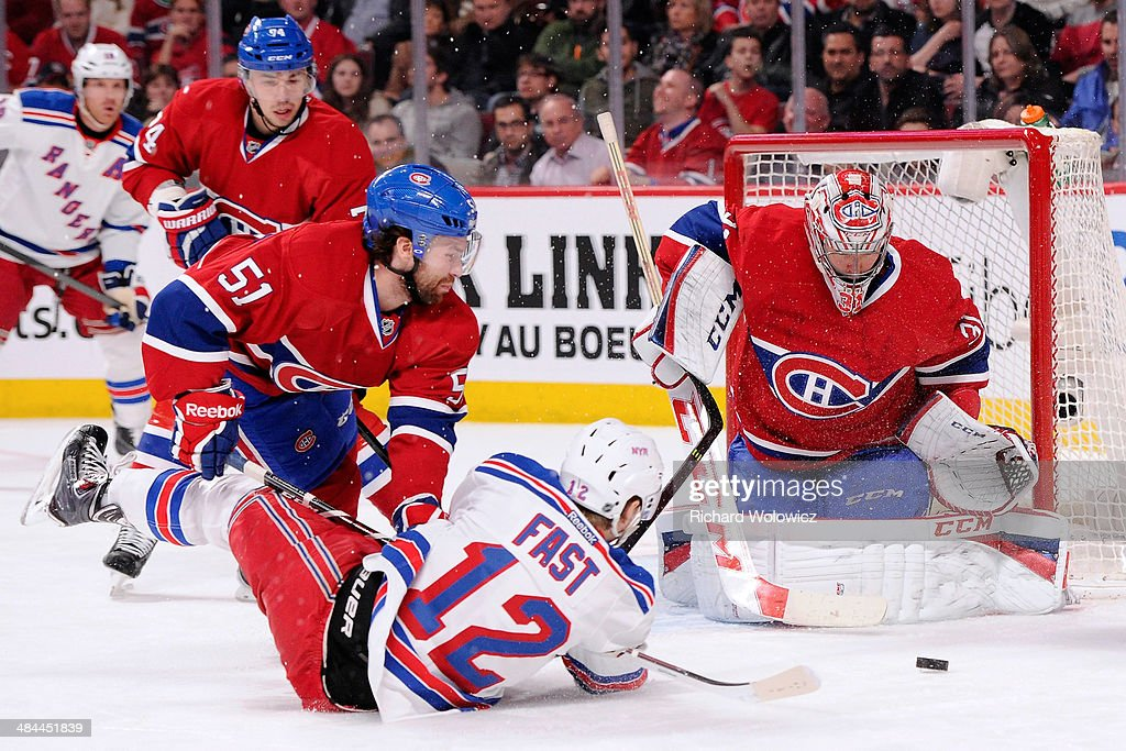 Carey Price #31 of the Montreal Canadiens gets down to stop the puck in front of teammate David Desharnais #51 and Jesper Fast #12 of the New York Rangers during the NHL game at the Bell Centre on April 12, 2014 in Montreal, Quebec, Canada.