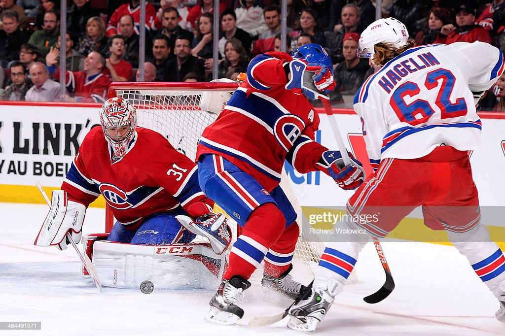 <a gi-track='captionPersonalityLinkClicked' href=/galleries/search?phrase=Carey+Price&family=editorial&specificpeople=2222083 ng-click='$event.stopPropagation()'>Carey Price</a> #31 of the Montreal Canadiens gets down to stop the puck in front of teammate <a gi-track='captionPersonalityLinkClicked' href=/galleries/search?phrase=Andrei+Markov&family=editorial&specificpeople=204528 ng-click='$event.stopPropagation()'>Andrei Markov</a> #79 and <a gi-track='captionPersonalityLinkClicked' href=/galleries/search?phrase=Carl+Hagelin&family=editorial&specificpeople=4465394 ng-click='$event.stopPropagation()'>Carl Hagelin</a> #62 of the New York Rangers during the NHL game at the Bell Centre on April 12, 2014 in Montreal, Quebec, Canada. The Canadiens defeated the Rangers 1-0 in overtime.