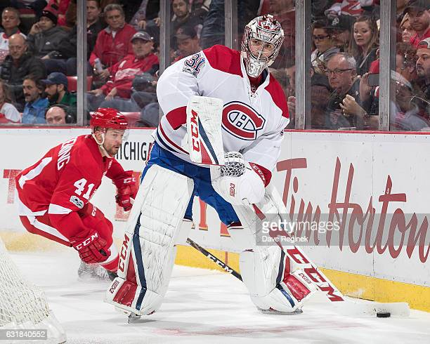 Carey Price of the Montreal Canadiens looks to pass the puck as Luke Glendening of the Detroit Red Wings skates in behind during an NHL game at Joe...