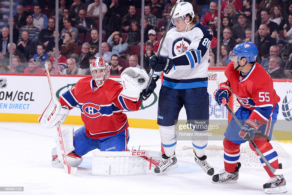 <a gi-track='captionPersonalityLinkClicked' href=/galleries/search?phrase=Carey+Price&family=editorial&specificpeople=2222083 ng-click='$event.stopPropagation()'>Carey Price</a> #31 of the Montreal Canadiens makes a glove save on the puck in front of <a gi-track='captionPersonalityLinkClicked' href=/galleries/search?phrase=Nik+Antropov&family=editorial&specificpeople=202953 ng-click='$event.stopPropagation()'>Nik Antropov</a> #80 of the Winnipeg Jets during the NHL game at the Bell Centre on January 29, 2013 in Montreal, Quebec, Canada. The Canadiens defeated the Jets 4-3.