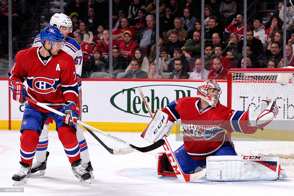 <a gi-track='captionPersonalityLinkClicked' href=/galleries/search?phrase=Carey+Price&family=editorial&specificpeople=2222083 ng-click='$event.stopPropagation()'>Carey Price</a> #31 of the Montreal Canadiens makes a glove save on the puck in front of teammate <a gi-track='captionPersonalityLinkClicked' href=/galleries/search?phrase=Andrei+Markov&family=editorial&specificpeople=204528 ng-click='$event.stopPropagation()'>Andrei Markov</a> #79 and <a gi-track='captionPersonalityLinkClicked' href=/galleries/search?phrase=Benoit+Pouliot&family=editorial&specificpeople=879830 ng-click='$event.stopPropagation()'>Benoit Pouliot</a> #67 of the New York Rangers during the NHL game at the Bell Centre on April 12, 2014 in Montreal, Quebec, Canada. The Canadiens defeated the Rangers 1-0 in overtime.