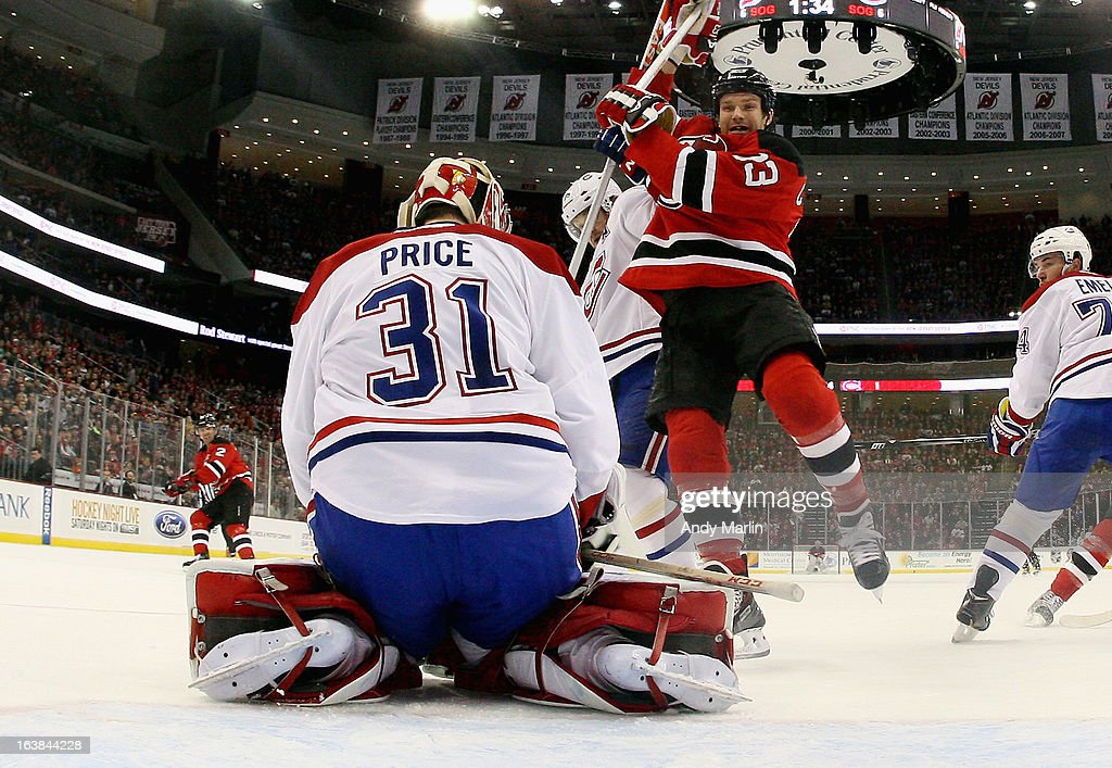 <a gi-track='captionPersonalityLinkClicked' href=/galleries/search?phrase=Carey+Price&family=editorial&specificpeople=2222083 ng-click='$event.stopPropagation()'>Carey Price</a> #31 of the Montreal Canadiens makes a save as David Clarkson #23 of the New Jersey Devils is checked in the crease during the game at the Prudential Center on March 16, 2013 in Newark, New Jersey.