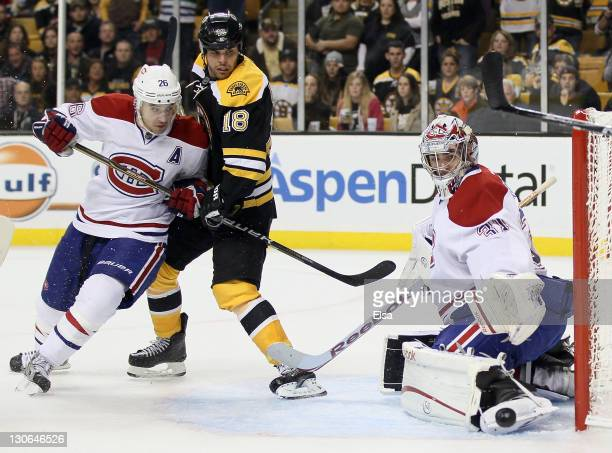 Carey Price of the Montreal Canadiens stops a shot by Nathan Horton of the Boston Bruins as Josh Gorges of the Canadiens defends on October 27 2011...