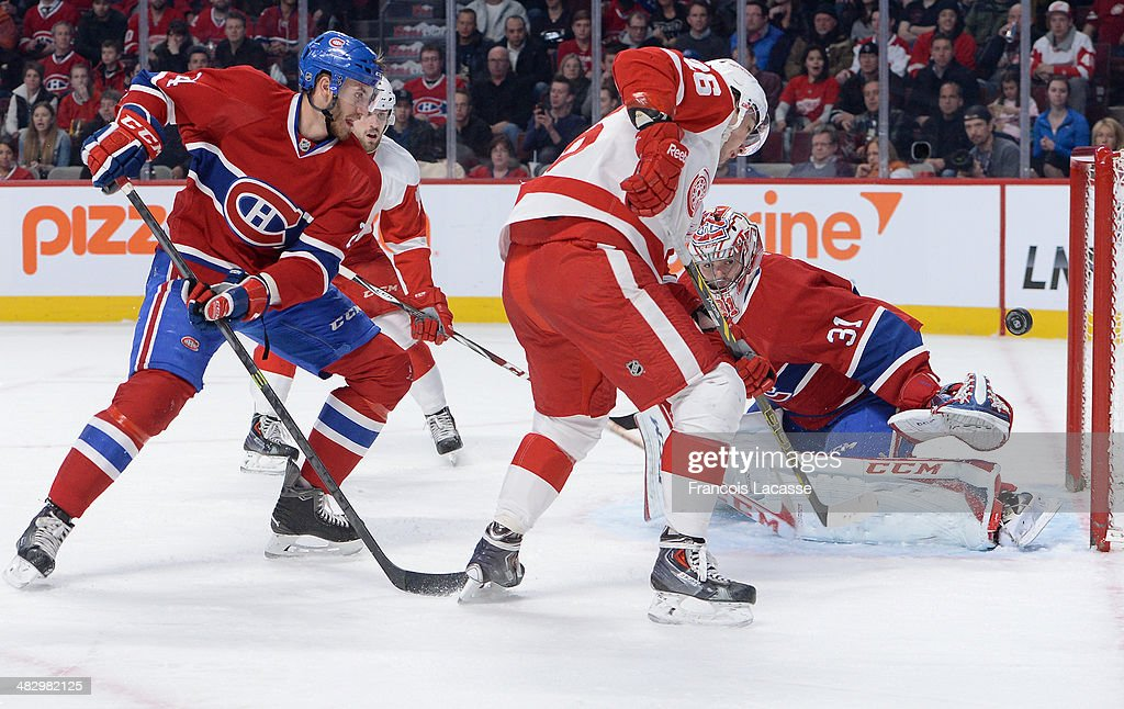 <a gi-track='captionPersonalityLinkClicked' href=/galleries/search?phrase=Carey+Price&family=editorial&specificpeople=2222083 ng-click='$event.stopPropagation()'>Carey Price</a> #31 of the Montreal Canadiens stops a shot by Tomas Jurco #26 of the Detroit Red Wings while <a gi-track='captionPersonalityLinkClicked' href=/galleries/search?phrase=Jarred+Tinordi&family=editorial&specificpeople=7029368 ng-click='$event.stopPropagation()'>Jarred Tinordi</a> #24 defends the goal during the NHL game on April 5, 2014 at the Bell Centre in Montreal, Quebec, Canada.