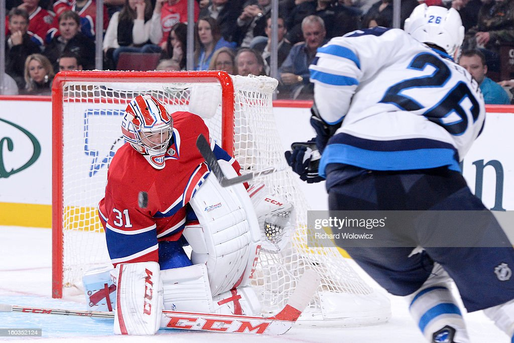 <a gi-track='captionPersonalityLinkClicked' href=/galleries/search?phrase=Carey+Price&family=editorial&specificpeople=2222083 ng-click='$event.stopPropagation()'>Carey Price</a> #31 of the Montreal Canadiens stops the puck on a shot by <a gi-track='captionPersonalityLinkClicked' href=/galleries/search?phrase=Blake+Wheeler&family=editorial&specificpeople=716703 ng-click='$event.stopPropagation()'>Blake Wheeler</a> #26 of the Winnipeg Jets during the NHL game at the Bell Centre on January 29, 2013 in Montreal, Quebec, Canada. The Canadiens defeated the Jets 4-3.
