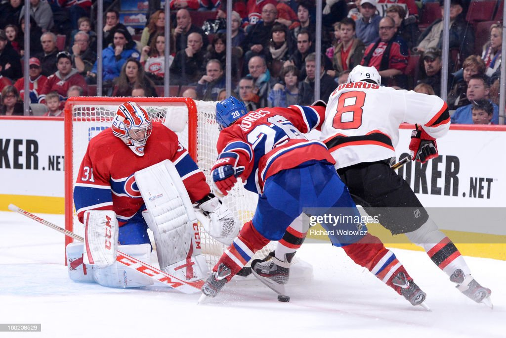 <a gi-track='captionPersonalityLinkClicked' href=/galleries/search?phrase=Carey+Price&family=editorial&specificpeople=2222083 ng-click='$event.stopPropagation()'>Carey Price</a> #31 of the Montreal Canadiens stops the puck on an attempt by <a gi-track='captionPersonalityLinkClicked' href=/galleries/search?phrase=Dainius+Zubrus&family=editorial&specificpeople=204779 ng-click='$event.stopPropagation()'>Dainius Zubrus</a> #8 of the New Jersey Devils during the NHL game at the Bell Centre on January 27, 2013 in Montreal, Quebec, Canada. The Canadiens defeated the Devils 4-3 in overtime.