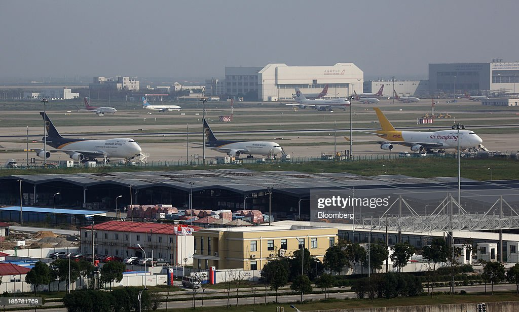 Cargo aircraft parked at Shanghai Pudong International Airport are seen from an observation deck at China (Shanghai) Pilot Free Trade Zone's Pudong free trade zone in Shanghai, China, on Thursday, Oct. 24, 2013. The area is a testing ground for free-market policies that Premier Li Keqiang has signaled he may later implement more broadly in the world's second-largest economy. Photographer: Tomohiro Ohsumi/Bloomberg via Getty Images