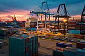 Cargo container and cranes on docks at dusk
