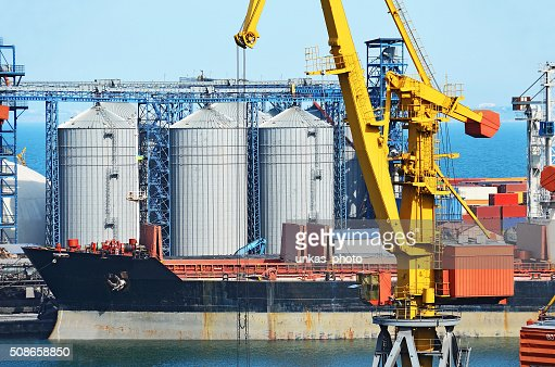 Cargo crane, ship and grain dryer : Stock Photo
