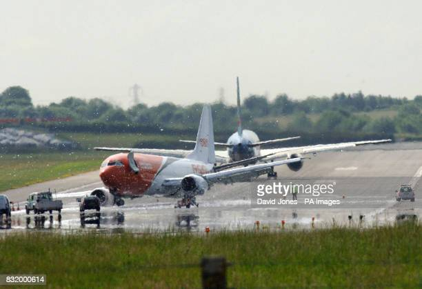 A TNT cargo plane lies damaged as a departing jet kicks up foam on the runway at Birmingham airport