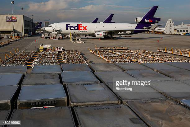 Cargo planes wait to be loaded with shipments as stacks of containers sit on the tarmac at the FedEx Corp distribution hub at Los Angeles...
