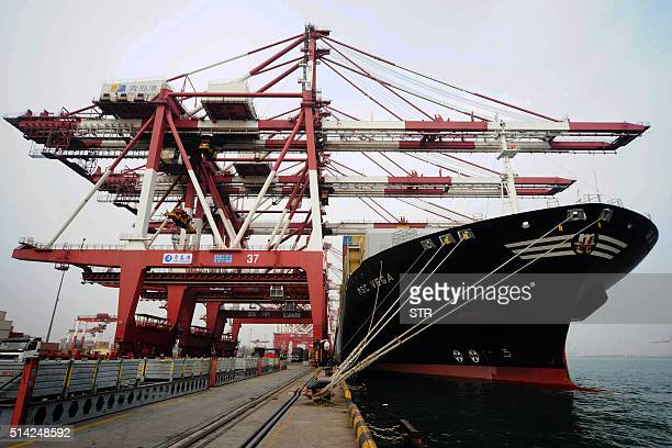 A cargo ship berths at a port in Qingdao east China's Shandong province on March 8 2016 China's exports saw their heaviest fall in nearly seven years...