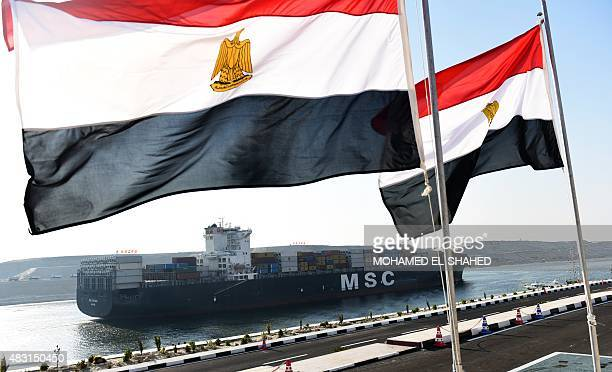 A cargo ship crosses a new waterway at the Suez Canal during its opening ceremony on August 6 in the port city of Ismailiya Egyptian President Abdel...