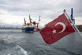 A cargo ship follows a ferry boat flying a Turkish national flag on the Bosporus Strait in Istanbul Turkey on Wednesday July 20 2016 Moody's Investor...