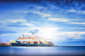 Cargo ship in the Trade Port, Shipping, Logistics, Transportation Systems, Container Cargo freight ship with working crane bridge in shipyard at twilight sky, Logistic Import Export background.