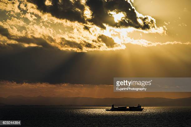 Cargo ship sailing on the sea, illuminated by sun spotlight