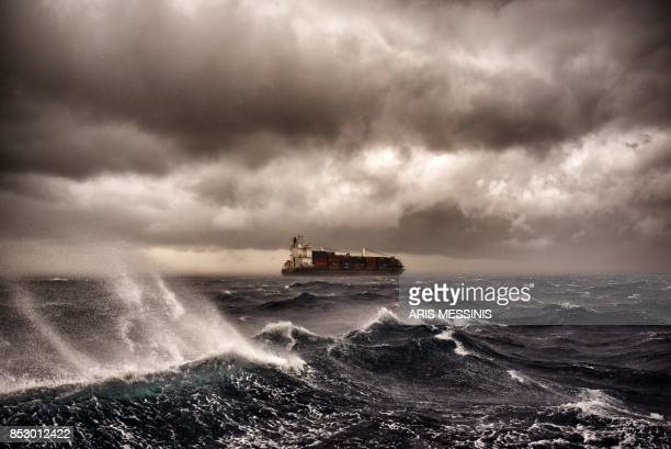 TOPSHOT A cargo ship sails on the Mediterranean sea during a thunderstorm some 20 naughtical miles from Malta on September 24 2017 / AFP PHOTO / ARIS...