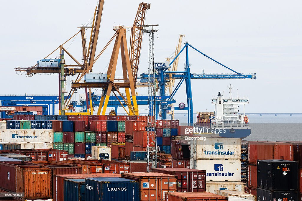 A cargo ship sails past shipping containers and gantry cranes at it leaves the main commercial port in Lisbon, Portugal, on Saturday, March 2, 2013. Prime Minister Pedro Passos Coelho is battling rising joblessness and lower demand from European trading partners as he raises taxes to meet the terms of a 78 billion-euro ($104 billion) aid plan from the European Union and the International Monetary Fund. Photographer: Mario Proenca/Bloomberg via Getty Images