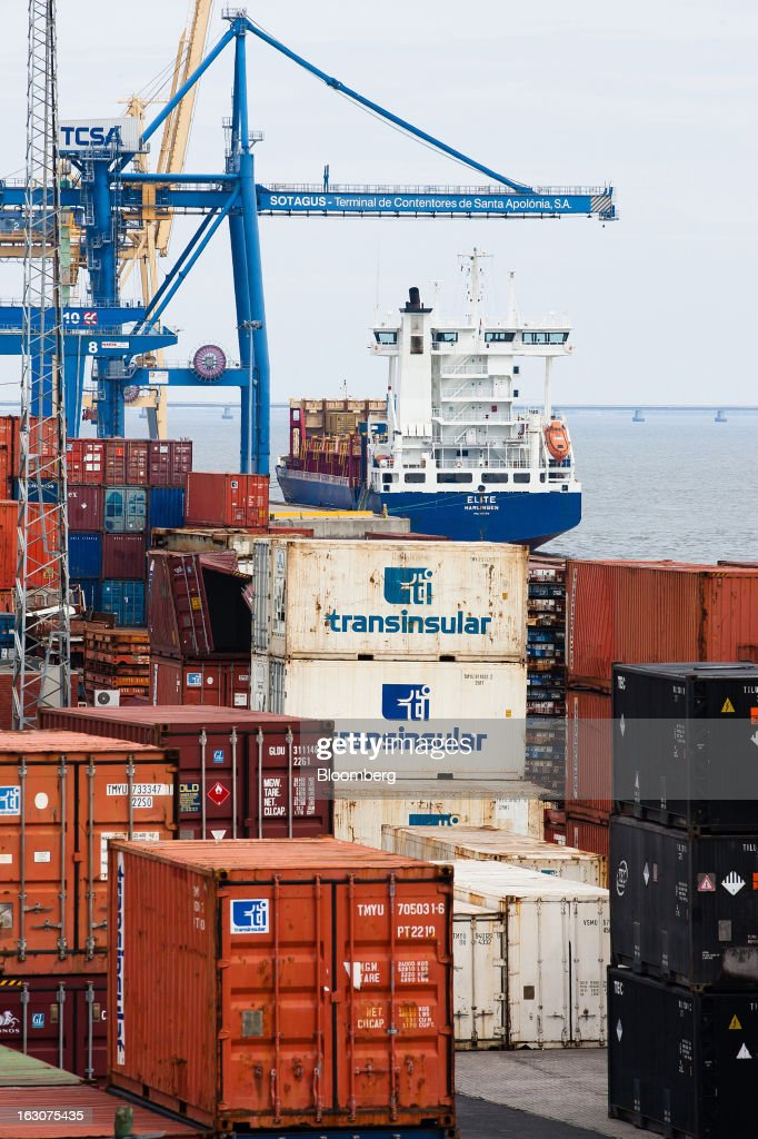 A cargo ship sails past shipping containers at it leaves the main commercial port in Lisbon, Portugal, on Saturday, March 2, 2013. Prime Minister Pedro Passos Coelho is battling rising joblessness and lower demand from European trading partners as he raises taxes to meet the terms of a 78 billion-euro ($104 billion) aid plan from the European Union and the International Monetary Fund. Photographer: Mario Proenca/Bloomberg via Getty Images