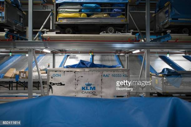 Cargo shipping crate stands as mail packages are transported on a conveyor inside the cargo center operated by Air FranceKLM Group at Schiphol...