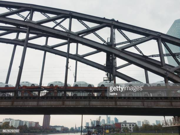 Cargo train carrying new cars over a bridge