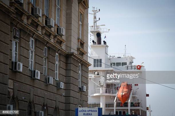 A cargo vessel is seen in the port of Rijeka Croatia behind a building in the center of the city on 23 July 2017