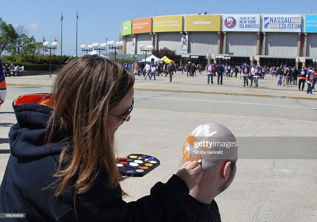 Carianne Varrecchia of Farmingville paints an Islanders logo on James Edmonds of Ronkonkoma prior to Game Three of the Eastern Conference Quarterfinals between the New York Islanders and the Pittsburgh Penguins during the 2013 NHL Stanley Cup Playoffs at the Nassau Veterans Memorial Coliseum on May 5, 2013 in Uniondale, New York.