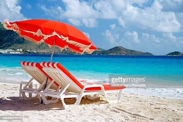 Caribbean, St. Martin, Orient Beach, Lounge chair and umbrella on a beach