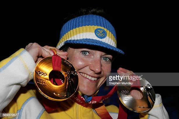 Carin Anna Olofsson of Sweden receives the Gold medal in the Womens Biathlon 125km Mass Start and posses with her other medal at the Medals Plaza on...