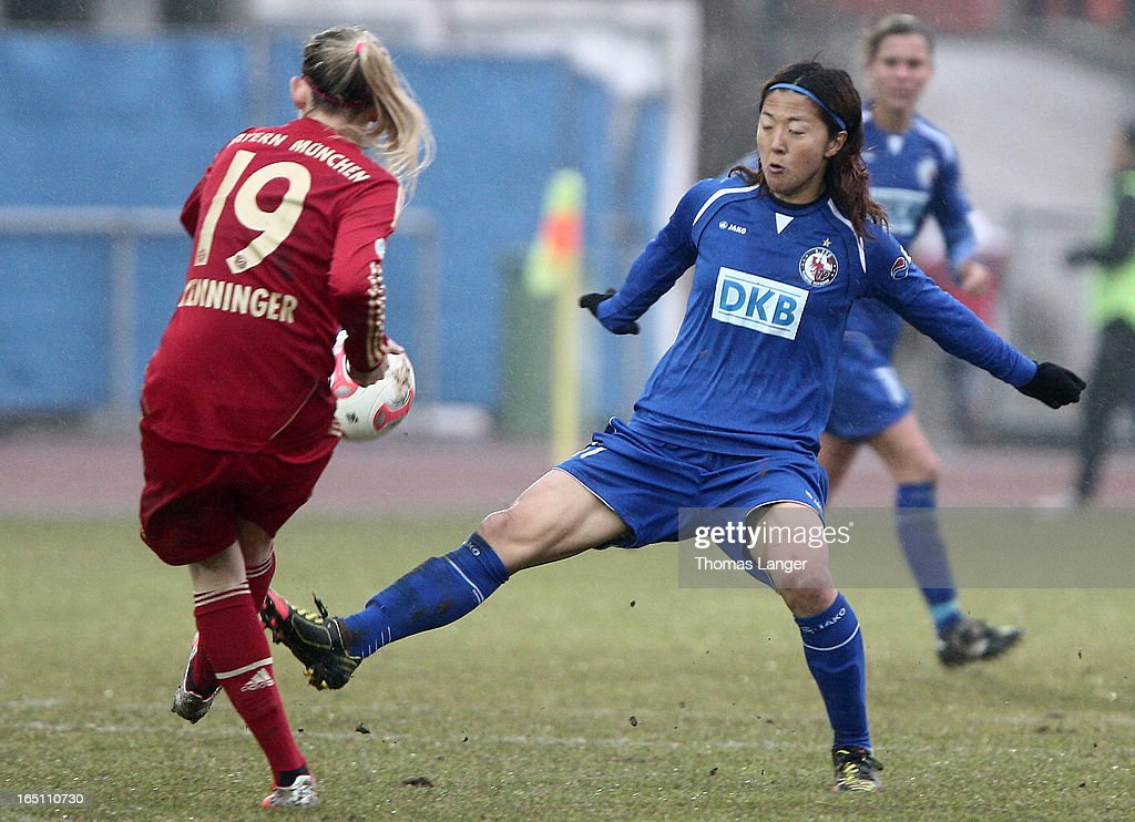 Carina Wenninger of Munich challenges Yuki Ogimi of Potsdam smiles during the Women's Soccer Bundesliga Match between Bayern Muenchen and 1. FFC Turbine Potsdam on March 30, 2012 in Aschheim, Germany.