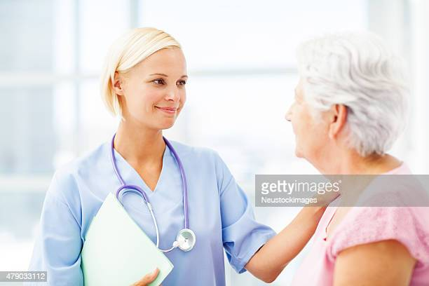 Caring Doctor Consoling Senior Patient In Hospital