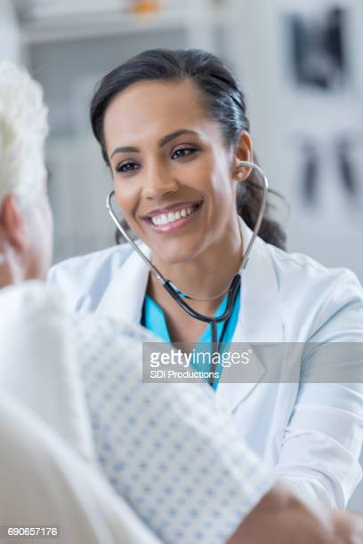 Caring female doctor examines senior male patient